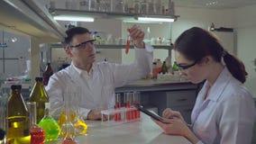 Chemika inżynier trzyma próbnej tubki z cieczem opowiada z uczniem zdjęcie wideo