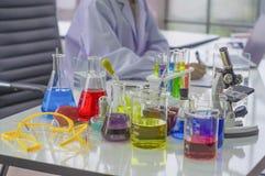 Chemiker bearbeiten Labor morgens, wenn die Probekörper mit bunten flüssigen Chemikalien arbeiten, Glasrohre Lizenzfreie Stockfotografie