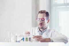 Chemiker, der eine Substanz in einer Petrischale stiring ist Lizenzfreie Stockfotografie