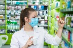 Chemiker, der Flasche mit Pillen im Drugstore betrachtet stockbilder
