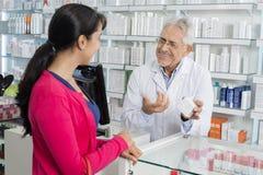 Chemiker Gesturing While Communicating mit weiblichem Kunden stockfotografie