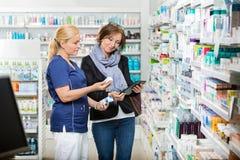 Chemiker Holding Eye Drops während Kunden-Anwendung Stockfotografie