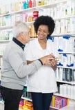 Chemiker-Looking At Senior-Mann beim Halten des Produktes Stockbild