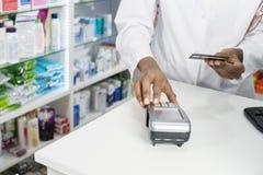 Chemiker-Pressing Buttons Of-Kartenleser At Counter Lizenzfreie Stockfotografie