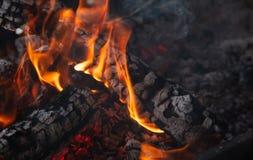 Cheminée avec le bois de chauffage brûlant et les flammes colorées sur le fond noir Fermez-vous avec des détails, l'espace Images stock