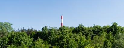 Cheminée, centrale dans la forêt verte Images libres de droits