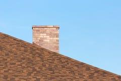 Cheminée de brique rouge sur maison moderne du toit OD de bardeau la nouvelle sous le ciel bleu le jour ensoleillé photographie stock