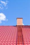 Cheminée de brique sur le toit rouge avec l'échelle en métal Photographie stock libre de droits