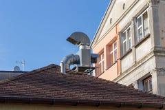 Cheminée de ventilation sur le toit avec la gouttière près de la vieille maison de rapport Image libre de droits