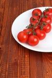 Cheminée des tomates de la plaque blanche sur le fond en bois Photo libre de droits