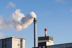 Cheminée industrielle avec des bâtiments de fumée et d'usine contre Photographie stock libre de droits