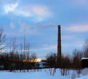 Cheminée industrielle dans les arbres au coucher du soleil Image libre de droits