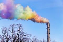 Cheminée industrielle métallique et une fumée d'arc-en-ciel Images stock