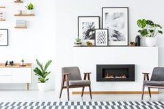Cheminée noire entre les fauteuils gris dans l'esprit d'intérieur d'appartement photos libres de droits