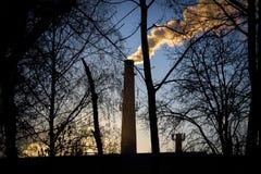 Cheminées d'usine sur le coucher du soleil Images libres de droits