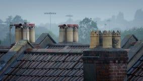 Cheminées sur des dessus de toit sous la pluie clips vidéos
