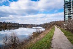 Chemin étroit fonctionnant à côté d'une rivière sous le ciel bleu avec des nuages Images stock