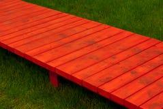 Chemin étroit rouge au-dessus de l'herbe Photographie stock libre de droits