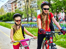 Chemin de bicyclette avec des enfants Filles portant le casque avec le sac à dos Photo stock