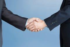 Chemin de coupure, hommes d'affaires se serrant la main sur le fond bleu Dou photos stock