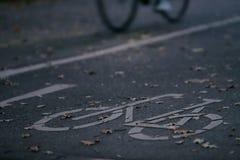 chemin de cycle dans la lumière de début de la matinée avec une bicyclette lente à l'arrière-plan - concept de permutation urbain images stock