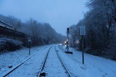 Chemin de fer et chemin de pied couvert dans la neige le jour foncé et sombre images stock