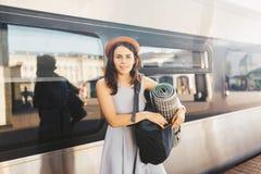 Chemin de fer et voyage de thème Jeune femme caucasienne de portrait avec le sourire toothy se tenant au fond de train de station image stock