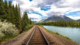 Chemin de fer le long de la rivière à côté d'une montagne photos libres de droits