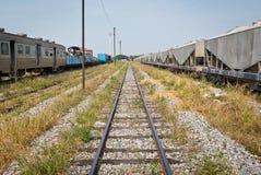 Chemin de fer regardant vers l'avant avec l'épave de train du côté gauche Photo stock