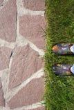 chemin de jardin de pierre, de pelouse et de pieds naturels en couvre-chaussures en caoutchouc Photo libre de droits