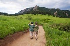 Chemin de montagne de promenade de deux garçons images stock