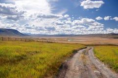 Chemin de route suivant la ligne de frontière sur un plateau des montagnes de montagne avec l'herbe verte Photo stock