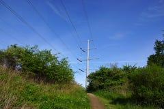 Chemin de saleté menant à la colline haute avec la puissance Polonais en métal dans le distan Image libre de droits