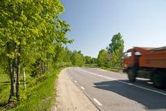 Chemin de terre avec le camion à benne basculante d'asphalte photographie stock