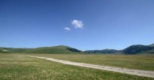 Chemin de terre dans Pian grand de Castellucio di Norcia photos stock