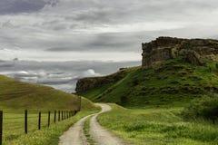 Chemin de terre de pays à côté d'un plateau Photographie stock libre de droits