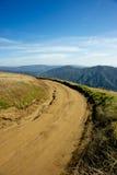 Chemin de terre en montagnes Photographie stock