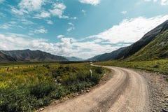Chemin de terre entouré par des collines de l'Altay Photographie stock libre de droits