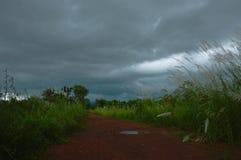Chemin de terre local en Thaïlande avec le fond foncé de nuage de pluie images stock