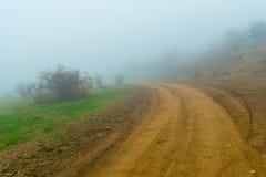 Chemin de terre menant dans le brouillard épais Paysage d'automne sur le DA brumeux photographie stock libre de droits
