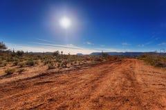 Chemin de terre par le désert Photographie stock libre de droits