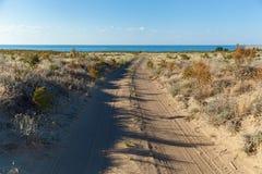 Chemin de terre vers la mer dans le désert Images stock