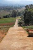 Chemin droit en bas de la colline Photos stock