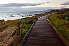 Chemin en bois le long de côté la mer au coucher du soleil Image stock