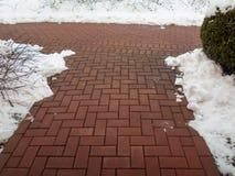 Chemin en pierre de jardin avec la neige Trottoir de brique photo stock