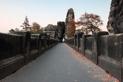Chemin en pierre du pont de Bastei avec des arbres et de formation de roche dans la porte de négligence de roche d'humeur d'autom photographie stock libre de droits