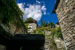 Chemin entre le vieux village de deux bâtiments en pierre photographie stock