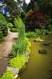 Chemin et étang aménagés en parc de jardin Photographie stock
