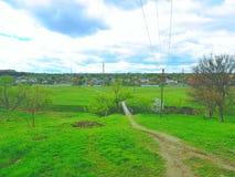 Chemin piétiné le long des côtés dont cultive l'herbe verte, arbres Ciel bleu Un village avec des maisons Photographie stock