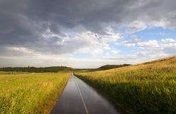 Chemin pluvieux de vélo à travers les champs et la Rolling Hills de prairie de campagne avec des nuages de pluie photo stock